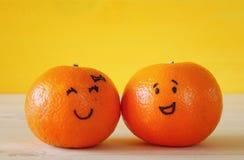 两棵柑桔的图象与拉长的兴高采烈的面孔的 图库摄影