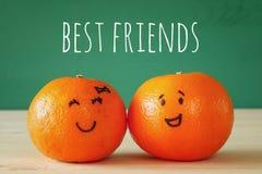 两棵柑桔的图象与拉长的兴高采烈的面孔的 库存照片