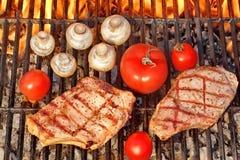 两棵牛排和菜炭灰被烤在发火焰BBQ格栅 免版税库存图片