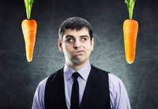 两棵红萝卜和商人 库存照片