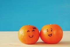 两棵逗人喜爱的柑桔的图象与拉长的兴高采烈的面孔的 免版税库存照片