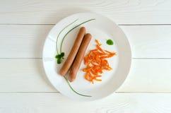 两棵香肠白色板材红萝卜顶视图 免版税库存图片