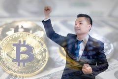 两次曝光亚洲商人庆祝成功与在美元钞票背景的金黄bitcoin, 免版税图库摄影