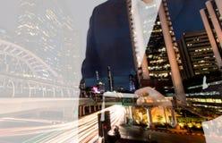 两次曝光商人手藏品和触摸屏巧妙的电话有现代城市背景 机动性, 免版税图库摄影
