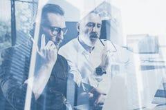 两次曝光概念 商人队做巨大工作讨论的在演播室 两个有胡子工友工作 免版税库存图片