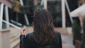 两次转向照相机的年轻可爱的妇女与走在街道的美好的微笑在一个现代大厦附近 股票视频