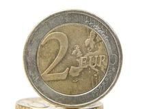 两欧元在另一枚硬币的硬币特写镜头 背景查出的白色 免版税库存照片