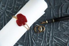 两残破的金黄结婚戒指与旨令文件离婚 离婚和分离概念 图库摄影