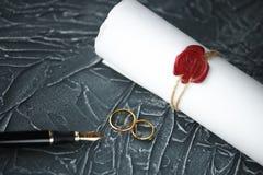 两残破的金黄结婚戒指与旨令文件离婚 离婚和分离概念 免版税图库摄影