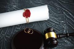 两残破的金黄结婚戒指与旨令文件离婚 离婚和分离概念 库存照片