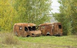 两没有轮子的生锈的汽车在森林背景站立 免版税库存照片