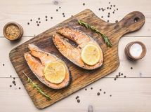 两油煎了新鲜的鲑鱼排用未磨过的胡椒,香料,在切板顶视图的柠檬 免版税库存图片