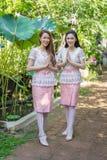 两泰国传统礼服的美女是薪水尊敬 免版税库存照片