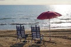 两海滩镶边了椅子在一个沙滩的一把桃红色伞下由海早晨 免版税库存照片
