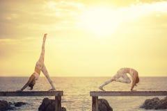 两演奏在木码头的妇女瑜伽姿势反对太阳上升的ov 图库摄影