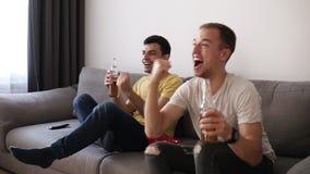 两激发喝啤酒和观看足球比赛的成人人室内在电视 庆祝胜利 关闭 股票录像