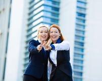 两激发女商人,给胜利标志,姿态的朋友 免版税库存图片