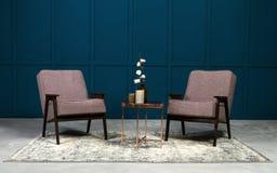 两灰色扶手椅子和铜咖啡桌和花瓶对此在蓝色屋子里 免版税库存图片