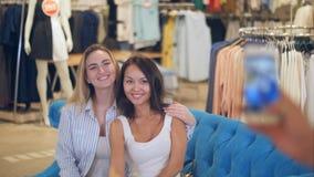 两点击在电话的妇女一张照片在购物中心 库存图片