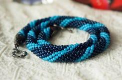 从两片树荫蓝色小珠的被编织的项链  免版税库存照片