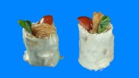 两片生鱼片寿司卷在孤立的蓝色背景上旋转成圆 股票录像