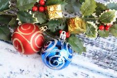 两片银色圣诞节球和霍莉叶子 库存照片