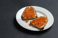 两片面包片用黄油和红色鱼子酱在一块白色板材 免版税库存图片