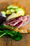 两片面包片的构成、蒜味咸腊肠、乳酪、绿皮胡瓜、红萝卜菠菜和片断  免版税库存照片