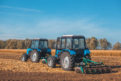 两犁领域的大蓝色拖拉机和去除以前被割的玉米遗骸  免版税库存照片