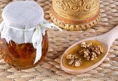 两瓶子蜂蜜和木匙子在土气背景 库存照片