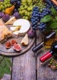 两瓶红色和白葡萄酒,葡萄,乳酪,黄柏,拔塞螺旋,在黑暗的背景的白面包 免版税库存照片