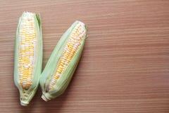 两甜玉米口气在木背景的 免版税库存图片