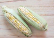 两甜玉米口气在木背景的 免版税图库摄影