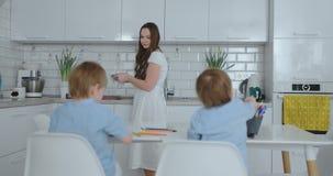 两男孩坐厨房光凹道学校搜寻的铅笔图 妈妈看孩子和微笑在 股票视频