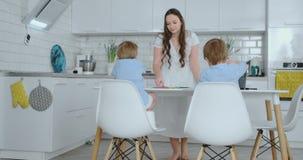 两男孩坐厨房光凹道学校搜寻的铅笔图 妈妈看孩子和微笑在 股票录像