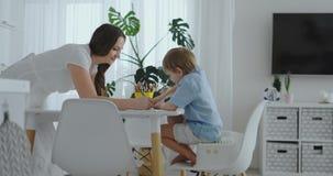两男孩坐厨房光凹道学校搜寻的铅笔图 妈妈看孩子和微笑在 影视素材