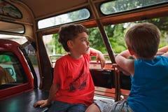 两男孩` s兄弟去有开放和看窗口的Windows的汽车 库存照片