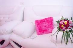 两白色沙发桃红色枕头和婚礼花束 免版税图库摄影