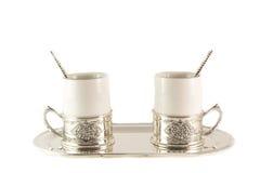两白色瓷有生来有福的咖啡杯在盘子 免版税库存照片