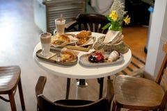 两的可口早餐在豪华旅馆用新鲜的热的饼,酸用莓果果酱、新月形面包和咖啡热奶咖啡 免版税库存图片