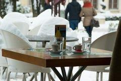 两的现代顶楼酒吧咖啡桌,与在消耗以后去的人,多雪的背景的舒适生活方式概念 免版税库存图片
