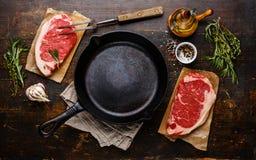 两的生肉牛排在煎锅附近 免版税库存照片