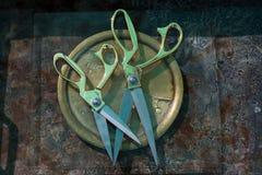 两相同在形状剪刀和不同肩并肩在一块圆的铜版在大小上说谎在清楚的玻璃下正方形, 图库摄影