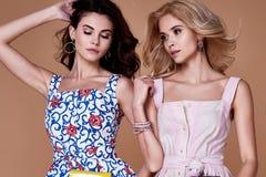 两秀丽妇女模型穿戴时髦的设计趋向衣物棉花 免版税库存照片