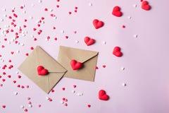 两种与多色甜冰糖心脏的工艺纸邮政信封 爱消息概念 免版税库存图片