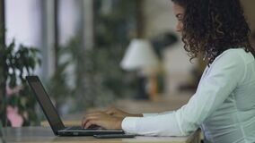 两种人种的在膝上型计算机的夫人键入的电子邮件在办公室,使用通信的计算机 影视素材