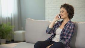 两种人种的女孩坐长沙发和预定的食物在电话,通信 影视素材