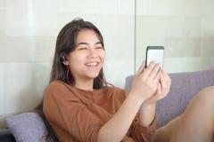 两种人种的青少年的女孩坐有智能手机的长沙发,笑 免版税库存图片