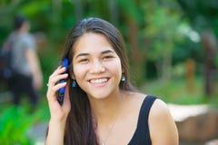 两种人种的青少年的女孩谈话在手机户外 免版税库存照片