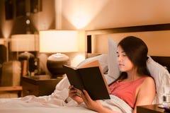 两种人种的青少年的女孩阅读书在床上在晚上 免版税库存图片